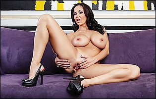 Busty brunette Ava Addams teasing with hot body on sofa