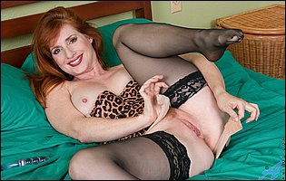 Amber Dawn in leopard lingerie and black nylons fucks herself with a glass toy