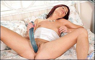 Sofia Matthews strips and sticks a long dildo in her vagina