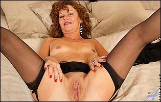 Hot mature redhead in black lingerie and stockings teasing