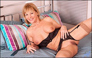 Elaine in sexy stockings sticks a dildo in her tight twat