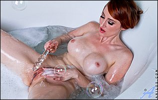 Holly Jane sticks a glass dildo in her tight pussy in the tub