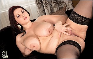Chubby beauty Ann Calis in black stockings teasing and playing with a dildo