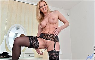 Lili Peterson in black stockings and leopard high heels fucks her pussy with a glass dildo