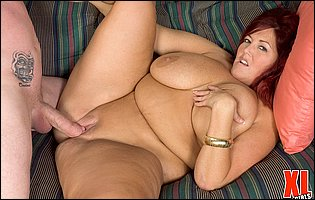 Plump redhead Peaches LaRue gives blowjob and gets fucked on sofa