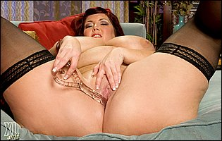 Peaches LaRue in black stockings and red heels posing and playing with a glass dildo