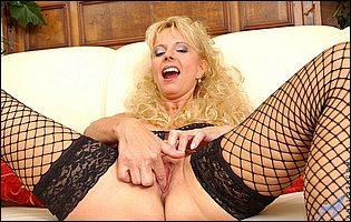 Mature blonde Merilyn in fishnet stockings fingering her cunt