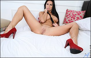 Hot brunette Nikkitta in red high heels teasing with tight body