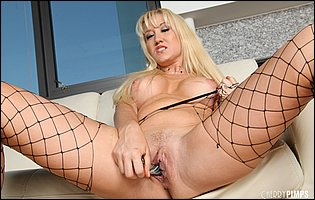 Alana Evans in fishnet stockings teasing with hot body and fucks her pussy with a glass dildo