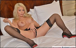 Riley Steele in black lingerie, stockings and heels posing for your pelasure in bedroom