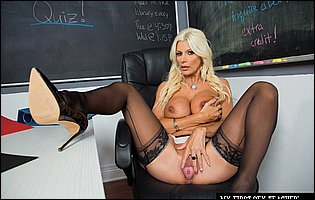 Beautiful teacher Brittany Andrews in black stockings and high heels posing in classroom