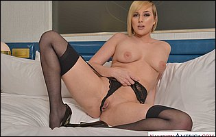 Kate England in black lingerie, stockings and high heels posing in bedroom