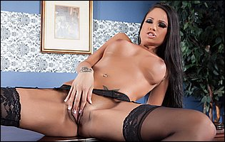 Raven Bay in black stockings and high heels posing on the desk