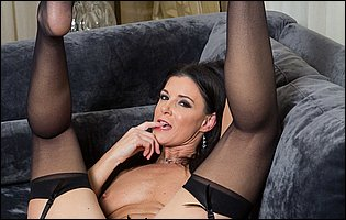 India Summer in sexy black lingerie, stockings and high heels posing for camera