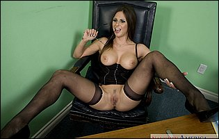 Rachel Roxxx in black corset and stockings posing and spreading legs in the office