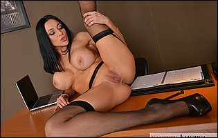 Audrey Bitoni in black stockings and high heels posing on the desk
